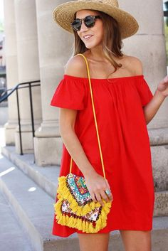 bright yellow bag and red off shoulder dress