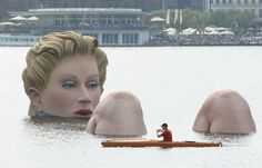 "Can't giants bathe in peace anymore? Boaters approach ""Die Badende"" (""The Bather""), a giant sculpture showing a woman's head and knees as if she were resting in the Binnenalster lake in Hamburg, Germany. Source: Weird News Photos 