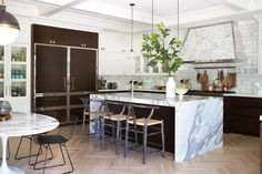 Hood fans are usually the hero of the kitchen but these riveted walnut panelled fridges are giving the hood a challenge