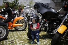 A Chinese boy wearing a helmet poses next to a Harley Davidson motorcycle in Zhejiang Province during the Harley Davidson National Rally in China
