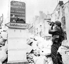 Caen: cameramen britannique de l'AFPU,  sergent J.H. Goddard du N°5 AFPU, Boulevard des Alliés, devant les ruines de l'hôtel Moderne, panneau de signalisation de la Feldkommandantur.