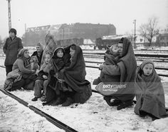 Huddling in blankets the only survivors of an original 150 Polish people who walked from Lodz in Poland to Berlin hoping to find food and shelter. They are waiting by a railway track hoping to be picked up by a British army train and given help.