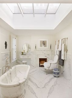 Lush marble throughout this cozy bathroom - including pedestal tub, floor, and fireplace surround, unifies the space with a singular element. Open ceiling design with skylight brightens up the space.