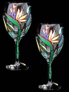 "This set of (2) wine glasses holds 16oz. and each stands 9"" tall. Our colorful ""Bird of Paradise"" flowers emerge from green boat shaped bracts bordered in vibrant red. This flowers arrow shaped tongues of brilliant blue are contrasted with it's outrageous orange petals."