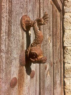 Aldaba de pez oxidada por el tiempo. Baltanás, Palencia