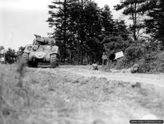 July 10, 1944: Soldiers of the 90th Infantry Division supported by a Sherman tank.