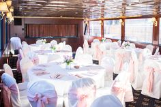 white tables with white chair covers and pink satin napkins with pink satin chair bows | pink roses and Queen Anne lace centerpieces | Princess Charter Cruises | Tigerlily Minneapolis Wedding Photography