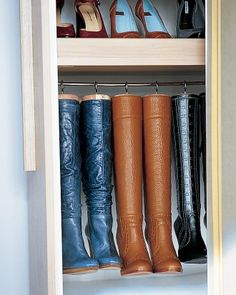 Boot Hangers: Homemade hangers preserve the shape of tall boots and maximize space. They're created by replacing the knobs on cedar boot trees with large cup hooks, which are screwed into the tops. The trees and boots then hang from a cafe-curtain rod.