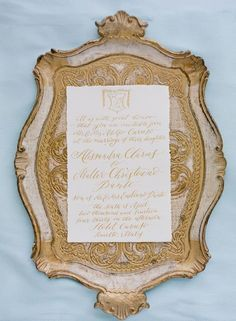 Old world gold and white invitation styled on tray Pinned by Magnolia Event Design www.magnoliaeventdesign.com