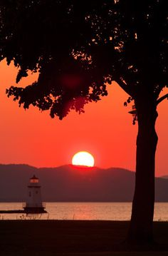 Sunset over lighthouse and nearby tree / Lake Champlain, Vermont, USA