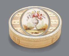 A GOLD AND ENAMEL SNUFFBOX, PROBABLY HANAU, CIRCA 1795 - the lid painted en plein with an oval panel of delicate flowers in an urn, the ground with engine-turned and incised ornament, the lid with pale blue and white enamel borders, sunray and crossed-S marks,