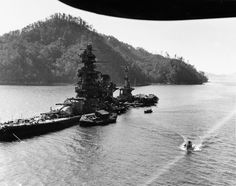The Japanese battleship Hyuga lies in shallow water of the Kure naval base. She received 21 direct bomb hits and another 30 that damaged her. The photo was taken by a crew member of USS Siboney (CVE-112).