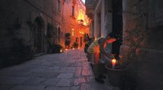 A small boy lighting one of the thousands of candles that light up the locality of Birgu during the annual festival of 'Birgufest'