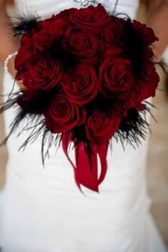 Red roses with black feathered decor/ Photo by Christie Pham Photography/ http://www.seasonsoflifeevents.com/