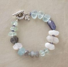 """Irregularly shaped faceted stones in watery hues evoke a tranquil pool. Aquamarine, moonstone, apatite and iolite are joined with a brushed sterling toggle clasp. Imported. Exclusive. Approx. 7-1/2""""L."""
