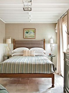 Bedroom Editing Hand-glazed woven raffia wallpaper wraps this bedroom in texture, while white wainscoting crisply contrasts the nubby texture of the upper walls. The wool blanket adds color, but the gray-based blue stripes almost read as neutrals.