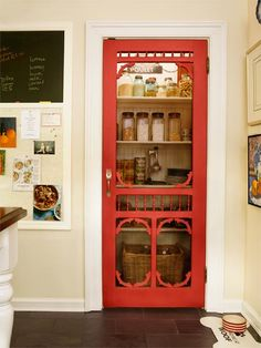 The pantry door was salvaged from the original house, painted tomato red, and outfitted with a pull fashioned from a fork.