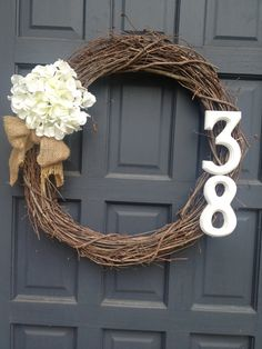 Grapevine wreath with burlap bow, hydrangea flower, and house numbers.