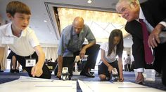 Nick Conklin (left) and Katrina Dang, from Avivara Oaks Middle School in Carlsbad, show Kareem Abdul-Jabbar and state schools chief Tom Torlakson their robot project during the STEM summit on Monday at the Sheraton Harbor Island. / photo by John Gastaldo • U-T