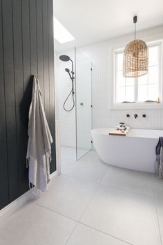 Room tour: A stunning deep blue, coastal luxe bathroom. Vertical straight stack white subway tiles, walk in shower, black tapware, freestanding bath, rattan pendant light. Bathroom goals and bathroom inspiration. Click on the image to go to the blog post for all the images