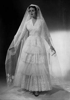 Model wearing a beautiful tiered lace wedding dress and long veil, December 1955.