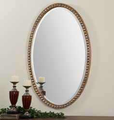 Uttermost Beadel Oval. This oversized, oval mirror features a beaded frame with a lightly antiqued, gold leaf finish and a gray wash.