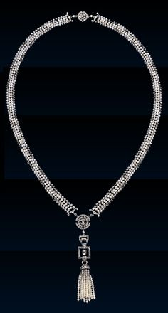 An Art Deco diamond seed-pearl sautoir, by Cartier, c,1920. Pearls interspersed at the sides with collet set diamonds strung into a flat ribbon chain terminating at one end with batons and a clasp of diamond, circles, and at the front with batons linked to another larger ornament of circles, joined to a Greek key motif attached by a double loop to a square rock crystal plaque outlined in diamonds and centred on a collet set diamond, suspending a diamond capped pearl tassel. #Cartier #ArtDeo