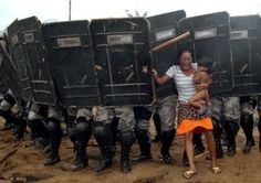 An Indigenous mother with her child attempts to block riot police as they evict the tribe from their homeland in Brazil.  — in Brazil.