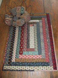 This primitive quilted table topper mat is a unique scrappy quilt of my own design. I just love how it turned out. It would wonderful for any table, bench, bedside table, in a cupboard, tucked in a basket, or in an antique doll bed. So many places for this prim beauty.This would make a wonderful gift for someone special. The quilted table topper/ table runner is made with strips of scrappy fabrics in 1800's reproduction material. It was machine sewn then hand quilted. It has a thin layer...
