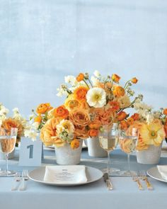 Bright bunches of sweetpeas, poppies, roses, ranunculus, and astrantia pop when placed in cloth-covered vases #blue #orange