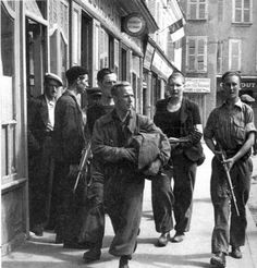 Guarded by armed members of the maquis, a German prisoner is marched through the streets of liberated Chartres.