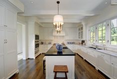Pricey Pads: Streamlined kitchen with long, linear kitchen island. Stained hardwood floors, white ...