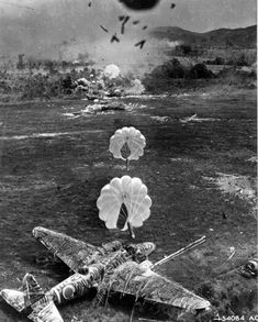 """Para-frag bombs fall toward a camouflaged Imperial Japanese Mitsubishi Ki-21, """"Sally"""" medium bomber, during an attack by the US Army Fifth Air Force against Old Namlea airport on Buru Island, Dutch East Indies (Indonesia), on October 15, 1944. A few seconds after this picture was taken the aircraft was engulfed in flames. The design of the para-frag bomb enabled low flying bombing attacks to be carried out with higher accuracy."""