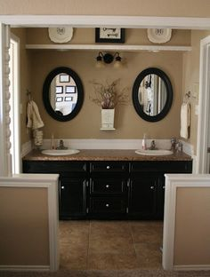 Master Bath -- double sinks, double mirrors, khaki paint, initial platters hung high about the vanity.