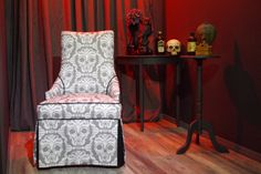 Scrollwork Skulls Boudoir Chair $340.00 Unusual curves and angles define this elegant boudoir chair - which is sure to be a statement piece perfect for any room.  The contrasting black welt highlights the the unique forms of this piece.  Upholstered in a luxurious Belgian linen and cotton blend fabric featuring The Calvarium's exclusive, hand-drawn Scroillwork Skulls pattern.  The skirt has kick pleats on the front corners, and knife pleats on the back.