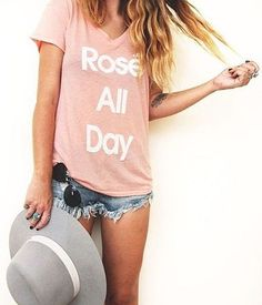 A pink t-shirt, distressed shorts, and a felt hat