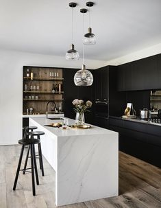 Black cabinetry and marble island bench