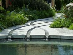 Beautiful criss-crossing rills, sculpted in granite slabs, run down to the shadow pool . Tom Hoblyn . Chelsea Garden 2011