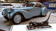 """""""The Art of Bugatti,"""" at the Mullin Automotive Museum near Los Angeles, honors the creative Bugatti family, whose French-built cars remain landmarks of design and engineering. Vw Group, Bugatti Cars, Bugatti Chiron, Car In The World, Hot Cars, Aston Martin, Motor Car, Custom Cars, Super Cars"""