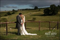 Dramatic wedding photo of couple kissing at Kingscote Barn in the Cotswolds, Gloucestershire. UK.