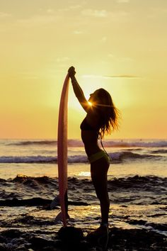 Alison Teal and her surfboard at sunset