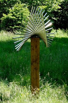 Stainless steel & oak Abstract Contemporary or Modern Outdoor Outside Exterior Garden / Yard Sculptures Statues statuary sculpture by artist Thomas Joynes titled: 'Spin (Swirling Repetitive Minimalist garden Yard statue)'
