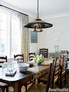 In the breakfast room, Urban Electric Co.'s Campion light fixture hangs above a rustic farmhouse table surrounded by rush chairs.