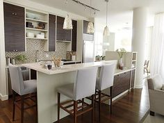 modern kitchen design with frosted glass retro pendant kitchen island lights, Macasar ebony veener kitchen cabinets, white, marble, counter tops, Saltillo ivory beige glass tiles backsplash and soft gray upholstered counter stools.