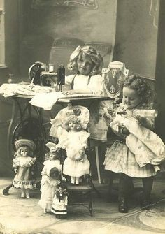 Two little Victorian girls playing house with many beautiful dolls and a sewing machine