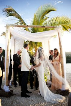 Love the way the bride's veil intertwines with the chuppah fabric.