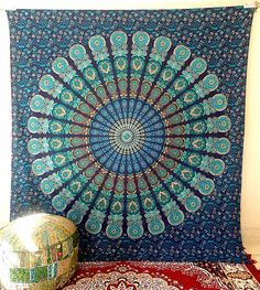 the creation of indian mandala pattern tapestry wall hanging. it has great combination of turquoise, aqua green on blue background base color. It is