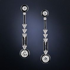 These wonderful, rare and all original drop earrings - circa 1925 - perfectly reflect the sophisticated Art Deco aesthetic. Each earring suspends a round European-cut diamond, ringed in dramatic black enamel, and surmounted by diamond set arrowheads dangling from a smaller, black enamel encircled diamond. Sleek, stunning and sexy vintage jewels! 1 and 5/16 inches long.