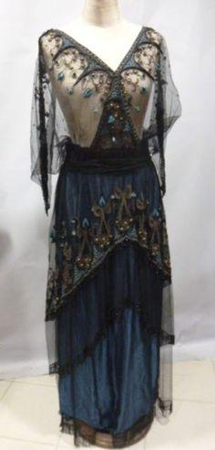 Robe du soir à l'orientale, vers 1914. Tulle de soie noir brodé de rinceaux, palmes et motifs de type égyptien en soie floche bleu vif et guilloché or. Jupe en satin bleu canard à volants de tulle brodé superposés soulignés d'une frange de perles de jais (doublure changée, camisole manquante)