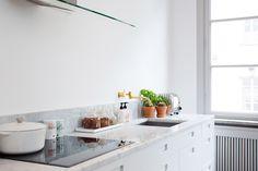 Vitt kök med marmorskiva och litet stänkskydd